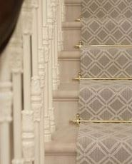 Beige geometric stair runner on steps with brass rods